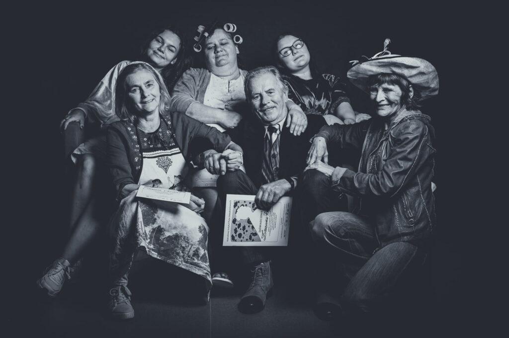 Na czarno-białym zdjęciu 6 osób. Jeden starszy mężczyzna naśrodku iwokół 5 uśmiechniętych kobiet. Dwie osoby trzymają dyplomy zNarodowego Czytania Pan Dulskiej.