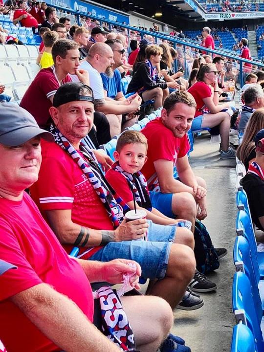 Na trybunach siedzi trzech mężczyzn imały chłopiec. Wszyscy ubrani są wczerwone koszulki. Chłopiec, orazjeden zmężczyzn założone mają szaliki klubowe. Patrzą wstronę obiektywu iuśmiechają się dozdjęcia. Wtle znajdują się inni kibice siedzący natrybunach.